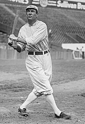A man wearing an old-style white baseball uniform swinging a baseball bat