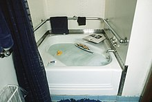 A small bathtub is visible in the center of the image. Bubbles, a rubber ducky, and a small floating boat can be seen in the tub, while two books, a soap bar, and a tooth paste tube can be seen around the rim of the bathtub.