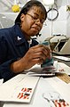 US Navy 030425-N-4953E-037 Postal Clerk 3rd Class Stephanie Hill cancels the stamp on mail in preparation for bagging up outgoing letter mail at the Post Office.jpg