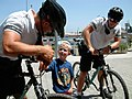 US Navy 030625-N-5821W-003 Master-at-Arms 3rd Class Vasko Thomas and Photographer's Mate 3rd Class Gunnar Curry Gorder, assigned to Sigonella's bike patrol unit, talk with a young shopper outside the base commissary.jpg