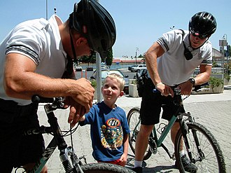 Naval security force sailors assigned to bike patrol duties. US Navy 030625-N-5821W-003 Master-at-Arms 3rd Class Vasko Thomas and Photographer's Mate 3rd Class Gunnar Curry Gorder, assigned to Sigonella's bike patrol unit, talk with a young shopper outside the base commissary.jpg
