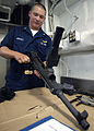 US Navy 040626-N-1512S-021 Aviation Electronics Technician 3rd Class William Lawrence, of Tifton, Ga., cleans an M240-D machine gun aboard amphibious assault ship USS Kearsarge (LHD 3).jpg