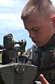 US Navy 040713-N-5055W-193 Pfc. David Tracy assigned to First Battalion, Twelfth Marine Regiment, sites the Howitzer 150 gun during an artillery live fire exercise.jpg