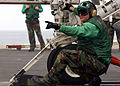 US Navy 050730-N-2805L-084 Aviation Boatswain's Mate 3rd Class Robert Lightner signals to the catapult operator to move the shuttle.jpg
