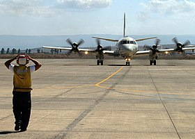 US Navy 060823-N-3013W-003 Aviation Ordnanceman 3rd Class Giancarlo Rosasarias of Los Angeles, Calif., directs the taxi pilot to straighten his direction of movement in order to properly park a P-3C Orion, after returning from.jpg