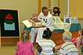 US Navy 070523-N-2908O-001 Boatswain's Mate 2nd Class Ryan Ward from Navy Operational Support Center (NOSC) Little Rock shares a laugh as he reads a book to a group of children in the youth services department of the Central Ar.jpg