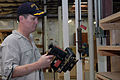 US Navy 070728-N-3705H-198 Cmdr. John Harber, intelligence officer aboard Nimitz-Class aircraft carrier USS Carl Vinson's (CVN 70), puts away tools in Habitat for Humanity's warehouse.jpg