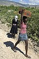 US Navy 080915-N-1508S-102 A Haitian woman carries a case of canned goods given to her by U.N. officials during relief efforts in areas of Haiti devastated by recent hurricanes.jpg