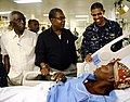 US Navy 100206-N-5345W-130 Capt. Sam Howard, commanding officer of the amphibious assault ship USS Bataan (LHD 5), right, visits Haitian patients in the medical ward with Haitian Prime Minister Jean-Max Bellerive.jpg