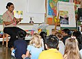 US Navy 100303-N-3666S-012 Boatswains Mate 2nd Class Rasheema Newsome, assigned to Commander, Navy Region Hawaii, reads a Dr. Seuss book to students at Lehua Elementary School.jpg