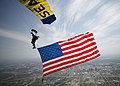 US Navy 100420-N-0000L-023 Aircrew Survival Equipmentman 1st Class Thomas Kinn, assigned to the U.S. Navy parachute demonstration team, the Leap Frogs, flies an American flag above Des Moines, Iowa.jpg