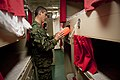 US Navy 100709-N-5319A-057 Peruvian Lt. Col. Renzo Corvetto looks at an emergency escape breathing device while touring a berthing space aboard aboard USS New Orleans (LPD 18).jpg