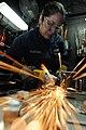 US Navy 101108-N-9132C-022 Hull Maintenance Technician 3rd Class Nelly Martinez grinds a TV bracket in the welding shop aboard the aircraft carrier.jpg
