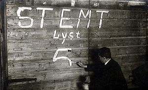 Dutch general election, 1918 - A man writing political slogans on a wooden fence in Amsterdam