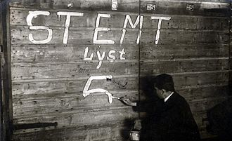 1918 Dutch general election - A man writing political slogans on a wooden fence in Amsterdam