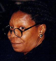 Middle-aged African-American woman with dreadlocks, looking away from the camera and smiling with her right cheek rested upon her folded hands.