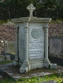 A granite, squared plinth with a column at each corner and a small cross on top of it, among other headstones