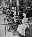 Workers at can sealing machines, published 1909.jpg