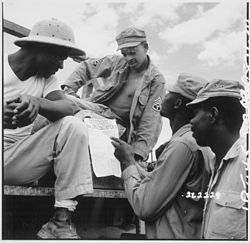 """""""... troops in Burma stop work briefly to read President Truman's Proclamation of Victory in Europe."""" - NARA - 531341"""