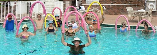 An aqua aerobics class, with participants in a swimming pool, holding up pool noodles