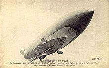 An airship with a pointed prow is seen from below; the gondola is visible, as are two ailerons, one port, one starboard