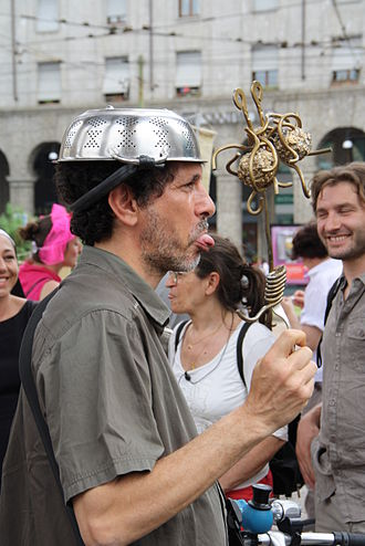Flying Spaghetti Monster - Pastafarian protester wears a colander while showing an icon of the Flying Spaghetti Monster