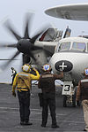 A U.S. Navy flight deck director salutes a pilot in an E-2C Hawkeye assigned to Airborne Early Warning Squadron (VAW) 117 on the flight deck of the aircraft carrier USS Nimitz (CVN 68) June 13, 2013, while 130613-N-ZG290-252.jpg