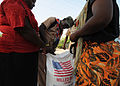 A boy scout with the Association Nationale des Scouts d'Haiti, cuts open a bag of rice for women at the soccer stadium in Port-au-Prince, Haiti 100216-N-HX866-004.jpg
