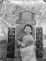 Albert Percy Godber's grandson Colin, seated beneath a carved sign for the Presbyterian Maori Mission at Te Teko. ATLIB 306486.png