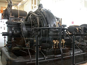 Varberg Radio Station - Alexanderson alternator in the Grimeton VLF transmitter. The drive motor is at the extreme right; the speed-increaser gearbox is just to its left. Note the bronze-colored shaft coupling.