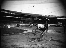 Photographie en noir et blanc d'un cycliste en activité.