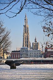 Snow-covered Antwerp, with government buildings in the background against a blue sky