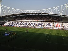 "A grandstand full of people holding up coloured cards spelling out the word ""Muamba"" and the number 6"