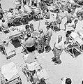 Badgasten in strandstoelen, in het midden een verkoopster die maïskolven staat t, Bestanddeelnr 255-1976.jpg