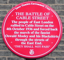 Red plaque from Tower Hamlets Environment Trust reading The Battle of Cable Street. The people of East London rallied to Cable Street on the 4th October 1936 and forced back the march of the fascist Oswald Mosley and his Blackshirts through the streets of the East End. 'They Shall Not Pass'