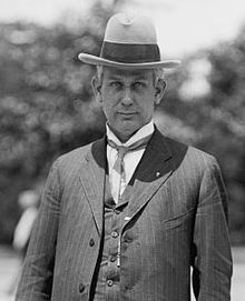 A black-and-white photo of a man in a suit and hat