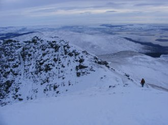Ben Lomond - A walker descending by the tourist route, seen from the summit in January 2010.