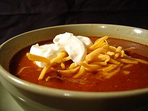 English: Bowl of chili with sour cream and cheese