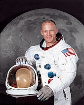 A portrait of a man wearing a space suit, with his helmet on the table in front of him. Behind him there is a large photograph of the lunar surface.