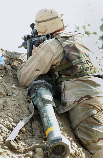 Forward Operating Base Chapman - A U.S. Army soldier from the 82nd Airborne Division looks down his M4 carbine's sights outside Camp Chapman in 2002.
