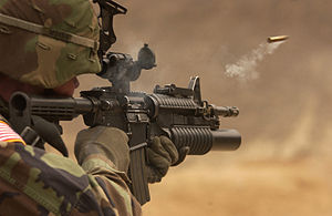 M4 carbine - An M4A1 just after firing, with an ejected case in mid-air; the M203 and M68 CCO are attached.