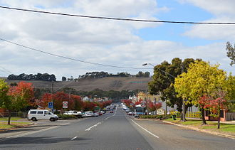 Casterton, Victoria - Henty Street (Glenelg Highway), the main street of Casterton. Note the Fleur-de-Lis and the name of the town carved into the hill in the background.