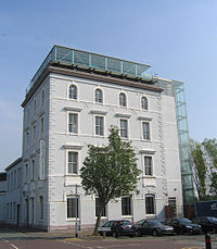 A four-storey building with four bays painted pale grey, with an extra glass storey on the roof and a glass lift on the right side; in front is a small tree and a row of parked cars