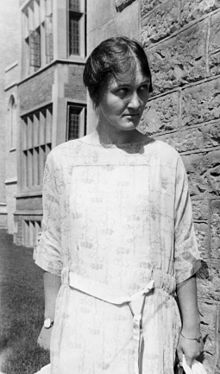 A woman in a white dress stands in front of a stone university building and looks down and to one side.