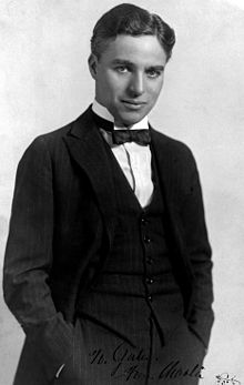 Photographie de Chaplin en costume avec un nœud papillon prenant la pose