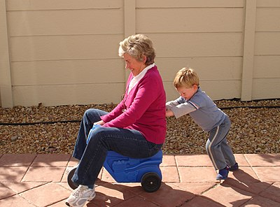 Child pushing grandmother on plastic tricycle.jpg