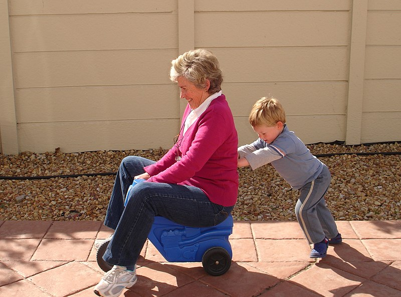 File:Child pushing grandmother on plastic tricycle.jpg