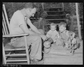 D.B. Henry, miner, who has worked for the company four years, repairs his children's wagon. He has made minor... - NARA - 540739.tif