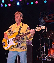 Dunn on stage playing bass guitar wearing a yellow Hawaiin shirt