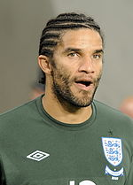 The head and shoulders of a man, with a cornrow hairstyle. On his shirt is a blue and white crest, featuring three lions.